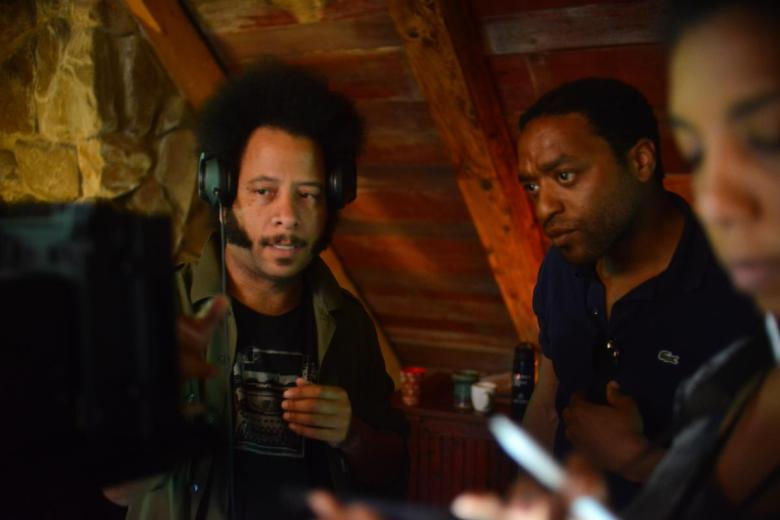 "Directing Fellow Boots Riley and Creative Advisor Chiwetel Ejiofor check the monitor during a shoot day for the project ""Sorry To Bother You."""