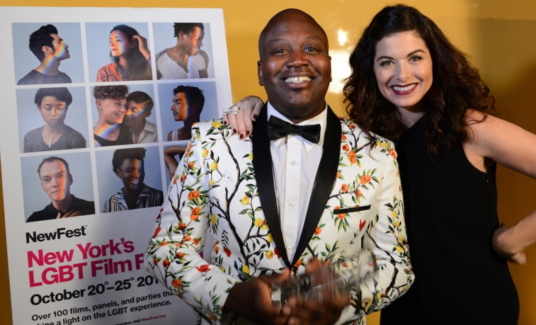 Tituss Burgess accepting the NewFest Voice & Visibility Award, presented by Debra Messing.