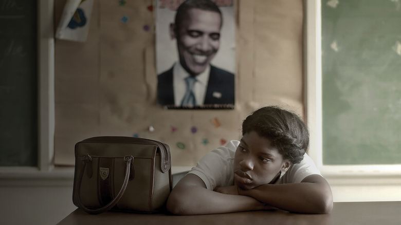 "Daje Shelton at school sitting at a desk under a poster of President Barack Obama while in ""In School Suspension"" after getting pulled out of class for talking back to a teacher. Film still from FOR AHKEEM. Courtesy of For Ahkeem film."