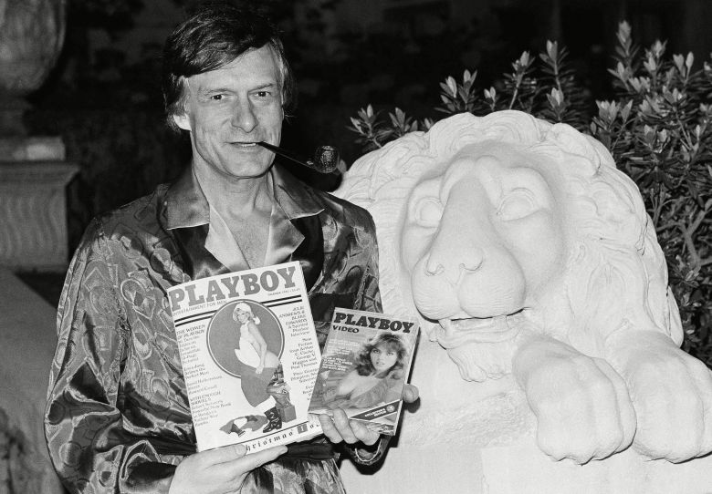 Playboy magazine publisher Hugh Hefner holds a copy of the magazine and a video cassette from the Playboy Channel, an all-night cable television venture Playboy Enterprises has undertaken, during an interview at the Playboy mansion in the Holmby Hills, Los Angeles, CalifHugh Hefner Los Angeles 1982, Los Angeles, USA