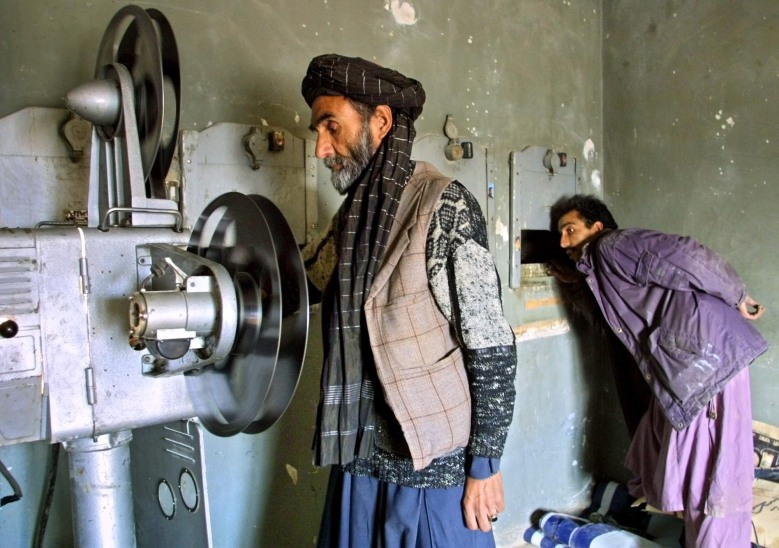 An Afghan man operates a movie projector while his assistant looks at the screen at a cinema in Mazar-e-Sharif, northern Afghanistan, . Mazar's residents on Tuesday celebrated the Eid-al-Fitr holiday by streaming to a movie theater open for the first time in four yearsAFGHANISTAN, MAZAR-E-SHARIF, Afghanistan