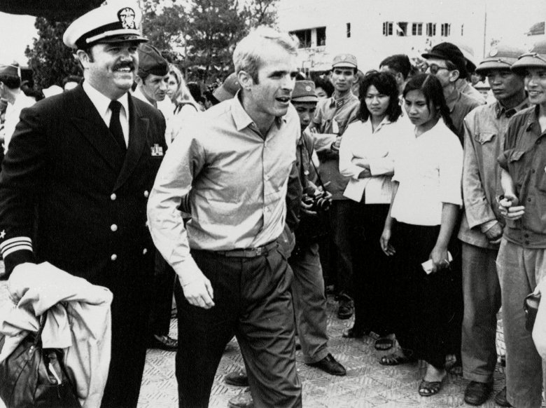 John S. McCain III is escorted by Lt. Cmdr. Jay Coupe Jr., public relations officer, to Hanoi's Gia Lam Airport after the POW was released