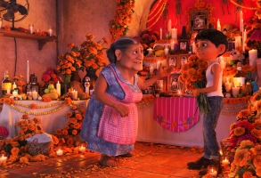 "COCO (Pictured) - DON'T FORGET THE SHOES – In Disney•Pixar's ""Coco,"" Abuelita (voice of Renée Victor) and Miguel (voice of Anthony Gonzalez) ensure that their home is adorned for Día de Muertos, including an elaborate ofrenda that holds several framed family pictures, flowers, candles, favorite foods and—because they are in the shoemaking business—shoes. ""Coco"" opens in n U.S. theaters on Nov. 22, 2017. ©2017 Disney•Pixar. All Rights Reserved."