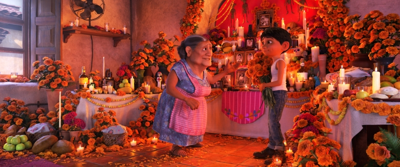 """COCO (Pictured) - DON'T FORGET THE SHOES – In Disney•Pixar's""""Coco,"""" Abuelita (voice of Renée Victor) and Miguel (voice of Anthony Gonzalez) ensure that their home is adorned for Día de Muertos, including an elaborate ofrenda that holds several framed family pictures, flowers, candles, favorite foods and—because they are in the shoemaking business—shoes. """"Coco"""" opens in n U.S. theaters on Nov. 22, 2017. ©2017 Disney•Pixar. All Rights Reserved."""