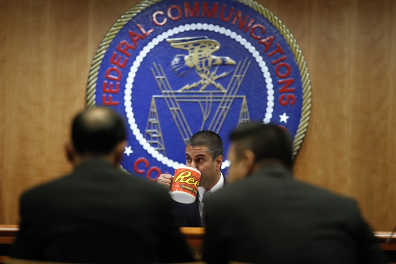 Federal Communications Commission (FCC) Chairman Ajit Pai takes a drink from a mug during introductions during an FCC meeting where they will vote on net neutrality, in WashingtonNet Neutrality, Washington, USA - 14 Dec 2017