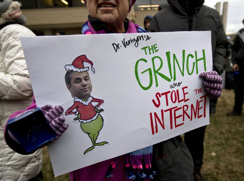 """Diane Tepfer holds a sign with an image of Federal Communications Commission (FCC) Chairman Ajit Pai as the """"Grinch who Stole the Internet"""" as she protests near the FCC, in Washington, where the FCC is scheduled to meet and vote on net neutrality. The vote scheduled today at the FCC, could usher in big changes in how Americans use the internet, a radical departure from more than a decade of federal oversightNet Neutrality, Washington, USA - 14 Dec 2017"""