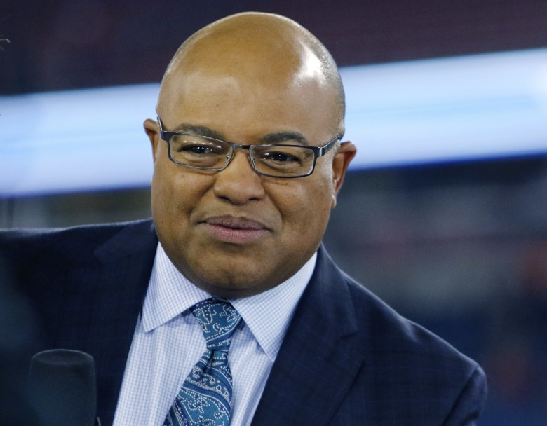 NFL sportscaster Mike Tirico sits on the sideline set before an NFL football game between the New England Patriots and the Atlanta Falcons, in Foxborough, MassFalcons Patriots Football, Foxborough, USA - 22 Oct 2017