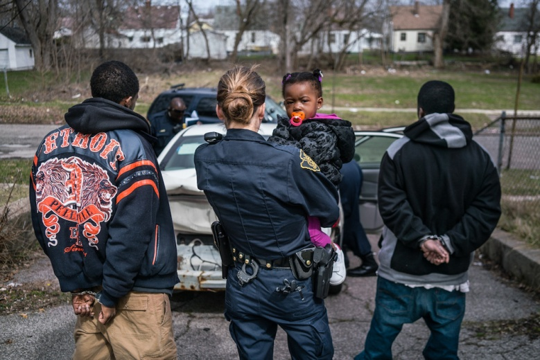Flint Town Season 1 Netflix Officer Bridget Balasko holds a small child while her father is being searched and questioned. The suspect on the left claimed to have just lost his job and didn't have anywhere to go so he was just hanging in his car with his daughter until the child's mother got off of work. At one point, the child was crying and Balasko reached into the suspect's pocket to pull out a pacifier for her.