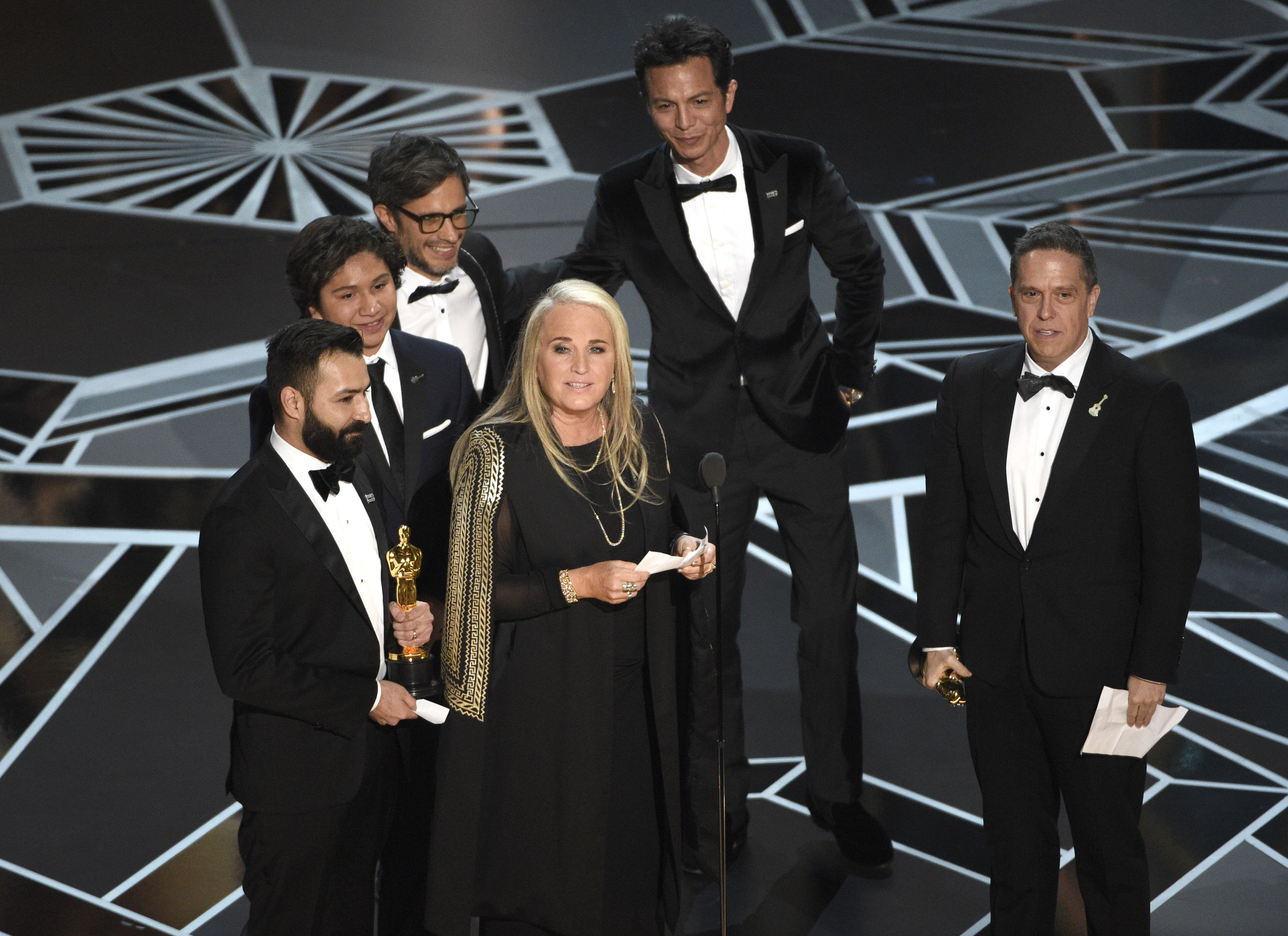 "Darla K. Anderson, Adrian Molina, Anthony Gonzalez, Gael Garcia Bernal, Benjamin Bratt, Lee Unkrich. Darla K. Anderson, center, and from back left, Adrian Molina, Anthony Gonzalez, Gael Garcia Bernal, Benjamin Bratt, and Lee Unkrich accept the award for best animated feature film for ""Coco"" at the Oscars, at the Dolby Theatre in Los Angeles90th Academy Awards - Show, Los Angeles, USA - 04 Mar 2018"