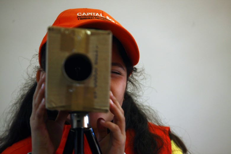 "A student looks through a cardboard box in the shape of a video film camera during a cinema class by Alicia Vega as part of her Children's Film Workshops at a school in the Penalolen neighborhood in Santiago, Chile, . Vega, who started teaching cinema to children 27 years ago, says film has a uniquely transformative power: ""My intention was never for them to become filmmakers, but for them to become better human beings, to discover themselves,"" says Vega, who recently documented her life's work in a book titled ""Film Workshop for Children,"" so that others might be inspired to follow her leadChile Shantytown Filmaker, Santiago, Chile"