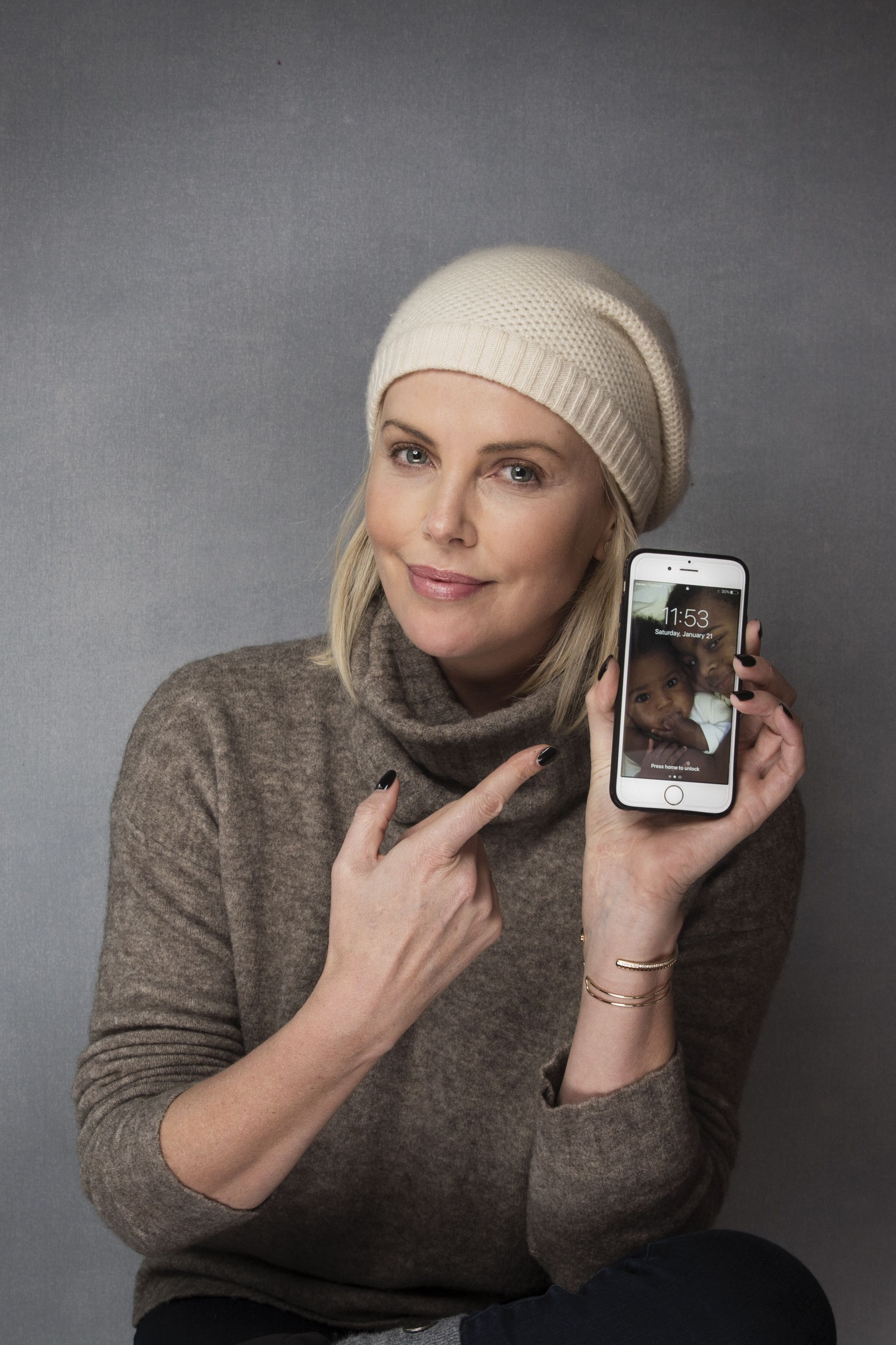 Actress Charlize Theron points to a photo of her children, August Theron and Jackson Theron as she poses for a portrait to promote Women's March on Main at the Music Lodge during the Sundance Film Festival, in Park City, UtahAPTOPIX 2017 Sundance Film Festival - Women's March on Main Portraits, Park City, USA - 21 Jan 2017