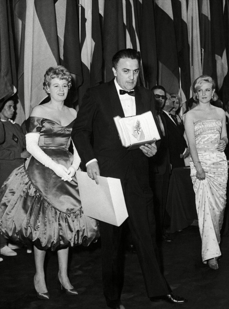 """Prizes were awarded on at the Cannes Festival Palace for this 1960 Film Festival. The winning film of the festival is """"La Dolce Vita"""" of Italian film director Frederico Fellini - after receiving his """"Palme d'Or"""" award, here is Fellini leaving the stage as on each side follow on American actress Shelly Winter, left, and French actress Nicole Courcel, rightFrance Cannes Film Festival Federico Fellini, Cannes, France"""