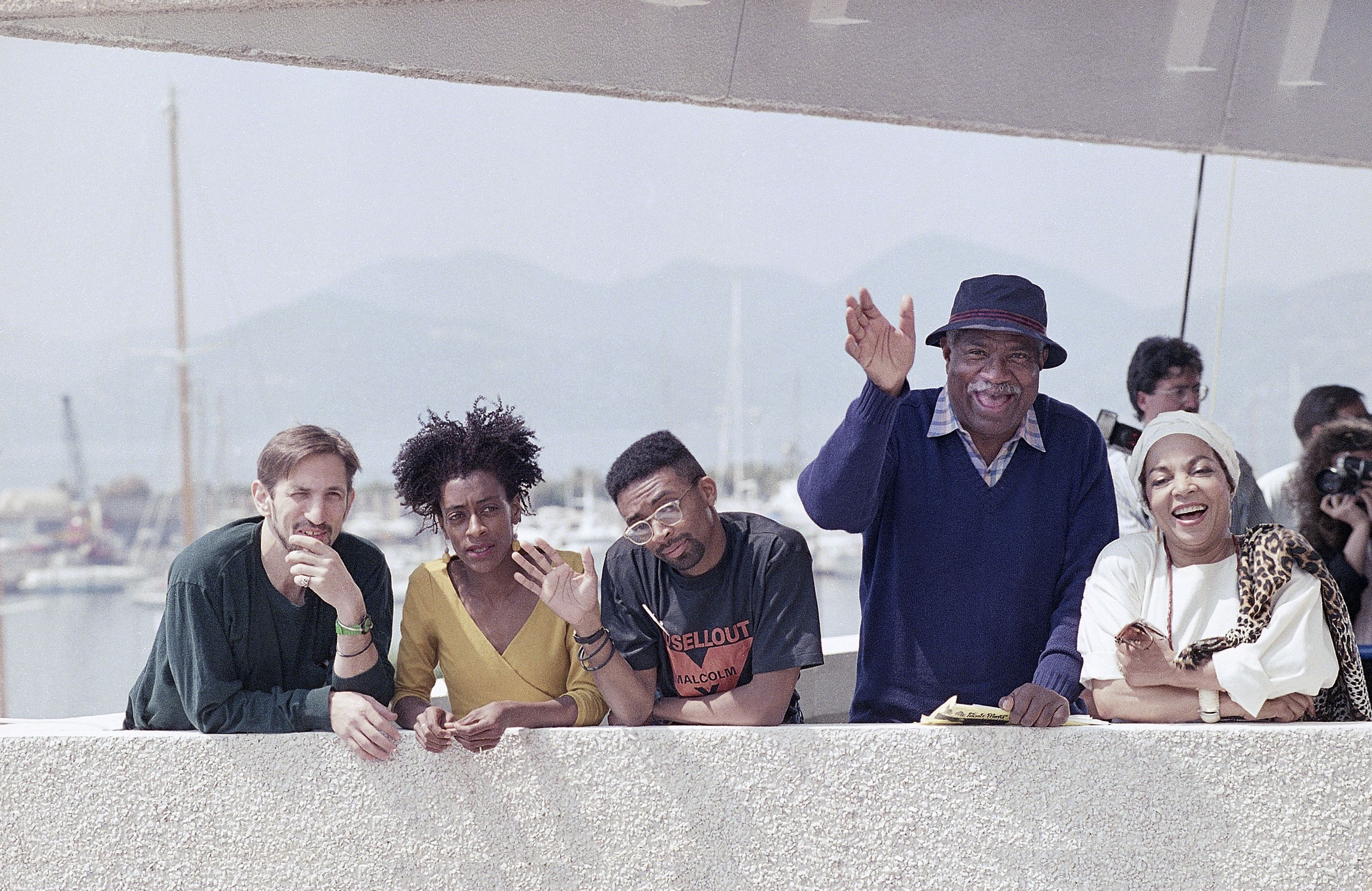 """American director Spike Lee, center, waves to photographers from the terrace of the Festival Palace in Cannes, France. Lee is promoting his film """"Do the Right Thing"""" at the Cannes Film Festival. Starring actors, from left, Richard Edson, Joie Lee, Ossie Davis and Ruby DeeSpike Lee Cannes 1989, Cannes, France"""