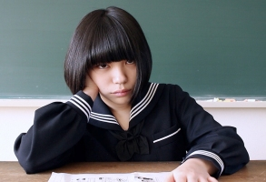 The titular Amiko played by Sunohara Aira sits at the teacher's desk, chalkboard behind her, in her high school uniform propping her head with one hand seemingly both board and annoyed as she stares right at the camera.