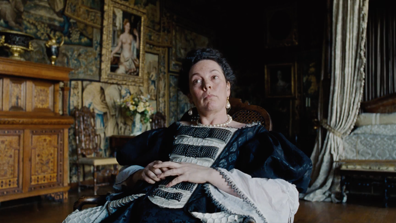 The Favourite (2018). Queen Anne, dressed in a puffy black and white dress and pearls, reclines on a chair in her ornate bedroom.