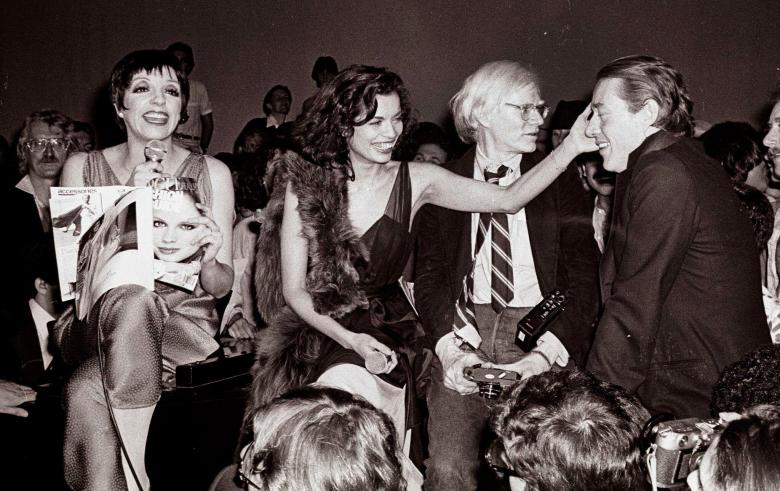 Liza Minelli, Bianca Jagger, Andy Warhol, and Halston at Studio 54. Photographer: Adam Scull. STUDIO 54. A film by Matt Tyrnauer. A Zeitgeist Films release in association with Kino Lorber.