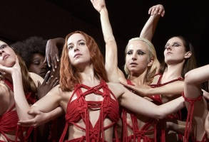 SUSPIRIA Dakota Johnson (center) and Mia Goth (center-left)