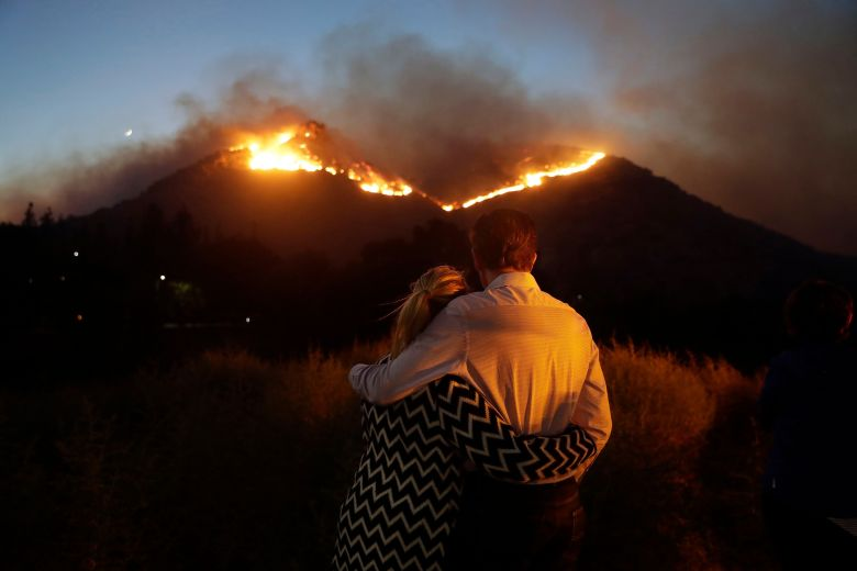Rober Bloxberg, Anne Bloxberg. Roger Bloxberg, right, and his wife Anne hugging while watching a fire at the top of a hill at her home in West Hill, CalifCalifornia Wildfires, West Hills, USA - Nov. 09 2018th