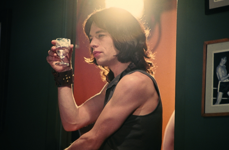 Mick Jagger raising a glass in Performance