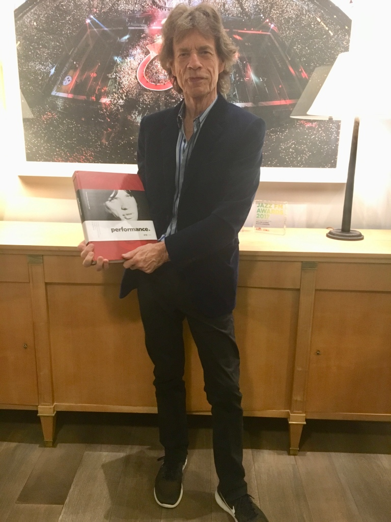 Mick Jagger holding a copy of Glennie's book