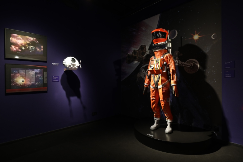 "Prints of space and spacecrafts by concept artist Roy Carnon (left) and a space suit worn in the Clavius Base scene in 2001: A SPACE ODYSSEY, as presented in ""Kubricks 2001: 50 Jahre A Space Odyssey"" exhibition at the DFF – Deutsches Filminstitut & Filmmuseum in Frankfurt am Main (2018). Photo credit: DFF/© Sophie Schüler"