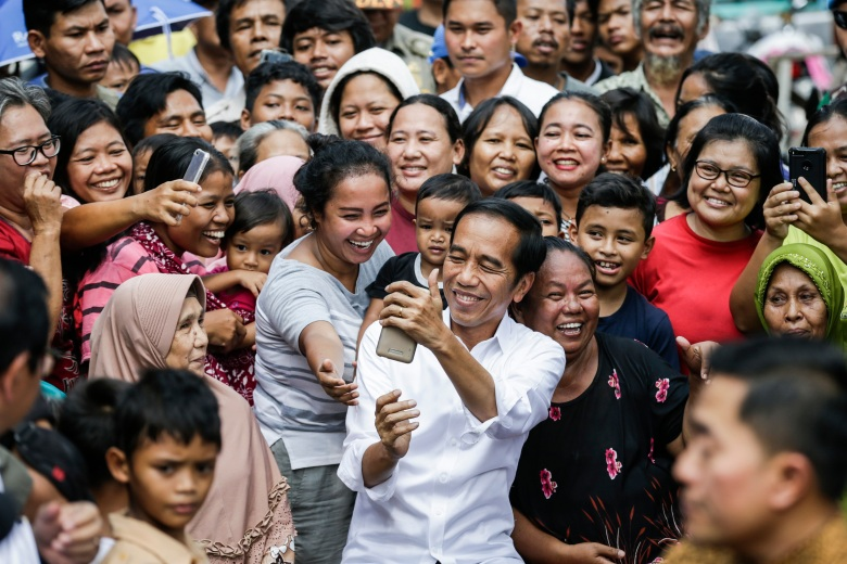 Indonesia's Incumbent President from the Indonesian Democratic Party of Struggle (PDIP) Joko Widodo (C) takes a selfie photograph with local residents after his victory speech following the announcement of the election results at a slum area in Jakarta, Indonesia, 21 May 2019. Incumbent Indonesian President Joko Widodo was re-elected after winning the presidential election over his rival, retired General Prabowo Subianto, the election commission announced early on 21 May 2019.Joko Widodo gives victory speech following the announcement of the election results in Jakarta, Indonesia - 21 May 2019