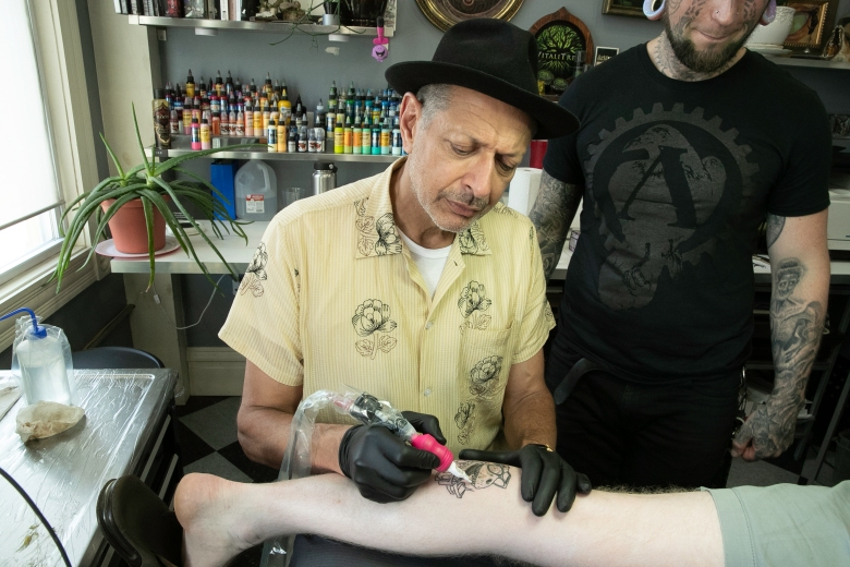 """In The World According to Jeff Goldblum, Jeff meets up with passionate artists and doting fans from the tattoo community. He attends one of the largest tattoo conventions in the country, and surprises fans at a Pittsburgh tattoo parlor for """"Jeff Goldblum Day."""" (National Geographic/George Lange)"""