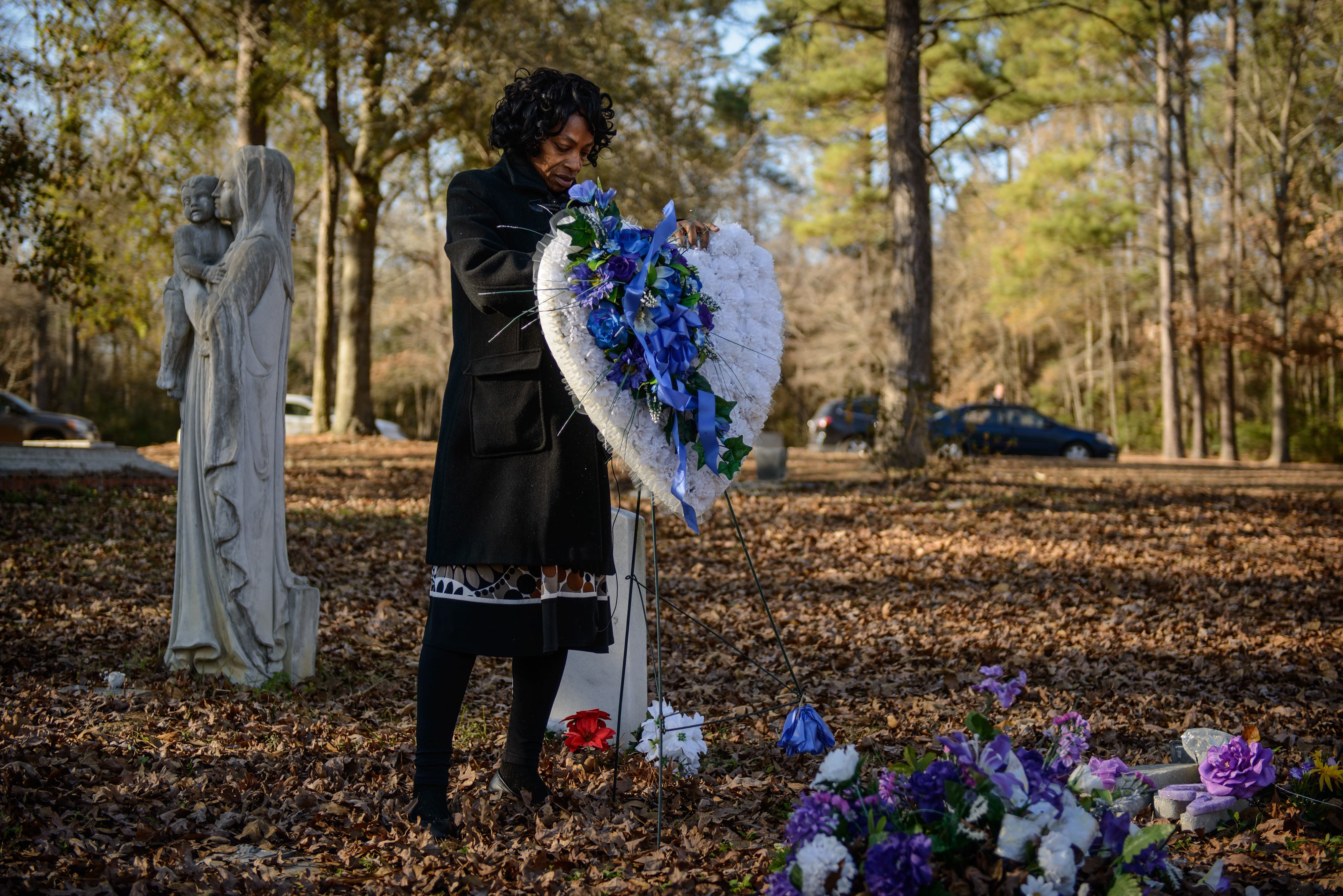 Claudia Lacy cleans up the flowers at the grave of her son, Lennon Lacy, Sunday, Dec. 14, 2014, at Old Shaw-Lacy Field Cemetery in Bladenboro, N.C. Lennon Lacy, a 17-year-old black teenager, was found dead on Aug. 29, 2014, hanging from a swing set in a trailer park in the rural community. Police ruled the death a suicide, but his family believe it was murder.