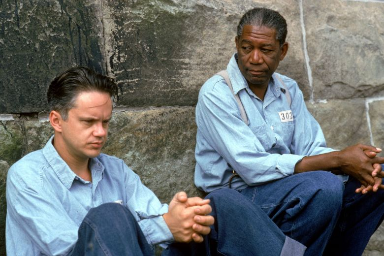 """Editorial use onlyMandatory Credit: Photo by ITV/Shutterstock (770117ra)'The Shawshank Redemption' Film Andy Dufresne (Tim Robbins), Right, and Ellis Boyd """"Red"""" Redding (Morgan Freeman) , Who Wears a Baseball Glove, Chat Whilst Kneeling Down, in the Prison CourtyardGTV ARCHIVE"""