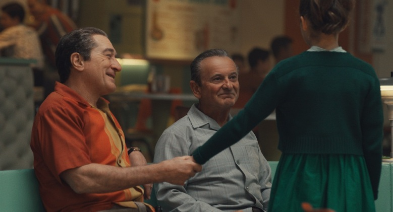 At a bowling alley, Frank Sheeran (Robert De Niro) attempts a show of warmth to his daughter Peggy (Lucy Gallina) in front of Russell Bufalino (Joe Pesci). © 2019 Netlfix US, LLC. All rights reserved.
