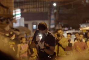 Manila, Philippines - A police officer takes a photo at a crime scene while a crowd watches on in the background. (Genius Loki Film and Violet Films/Alexander A. Mora)