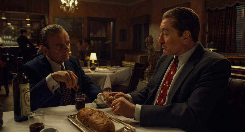 Dipping bread in wine, known as Intinction, speaks to the shared Catholic traditions of Russell Bufalino (Joe Pesci) and Frank Sheeran (Robert De Niro). © 2019 Netlfix US, LLC. All rights reserved.