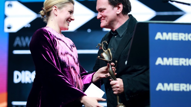 PALM SPRINGS, CALIFORNIA - JANUARY 02: (L-R) Greta Gerwig presents the Director of the Year award to Quentin Tarantino onstage during the 31st Annual Palm Springs International Film Festival Film Awards Gala at Palm Springs Convention Center on January 02, 2020 in Palm Springs, California. (Photo by Rich Fury/Getty Images for Palm Springs International Film Festival)