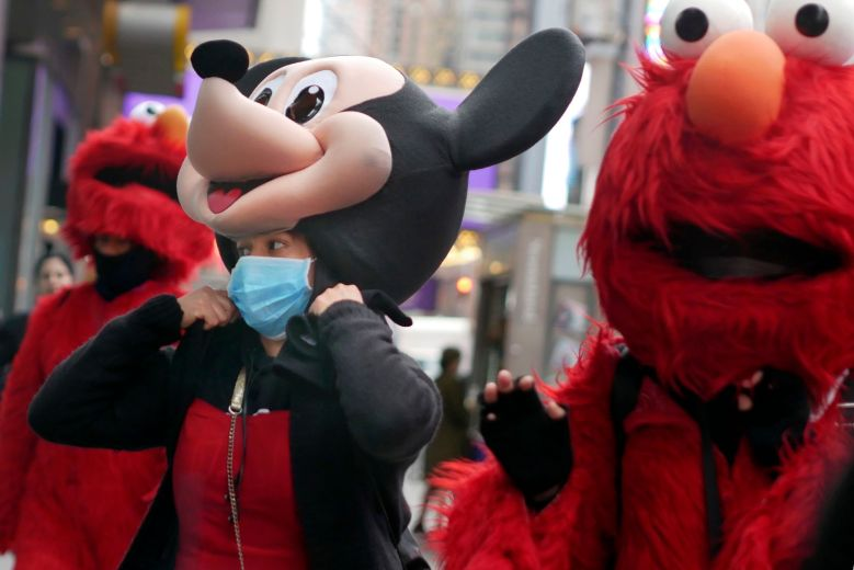 A woman wears a mask under her costume as she works in Times Square, New York, . New York state is shuttering schools and houses of worship for two weeks in part of a suburb and sending the National Guard there to help respond to what appears to be the nation's biggest cluster of cases of the coronavirusVirus Outbreak , New York, USA - 10 Mar 2020