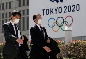Office workers wearing masks walk past the emblem of Tokyo 2020 Olympics in Tokyo, Japan, 18 March 2020. Japanese Prime Minister Shinzo Abe is still considering holding the Tokyo Olympics as scheduled despite the current coronavirus pandemic, after an emergency video conference with other G-7 leaders in fear over the outbreak of COVID-19 and the coronavirus.Tokyo 2020 Olympics still scheduled to go ahead despite coronavirus pandemic, Japan - 18 Mar 2020