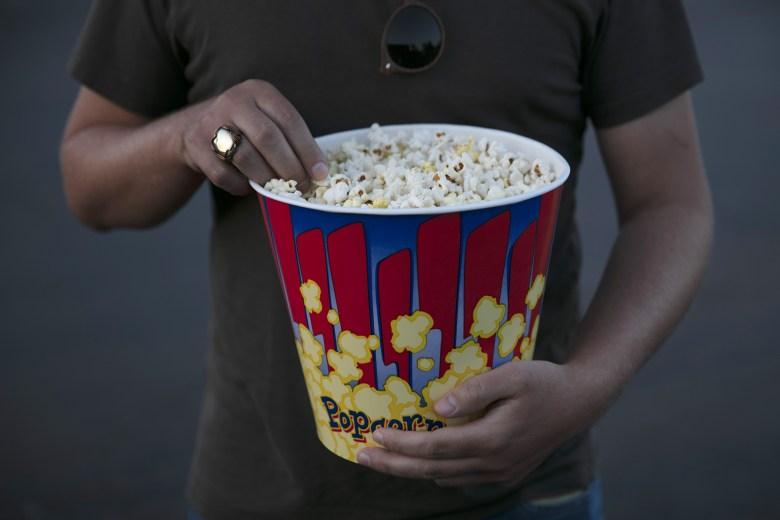 Moviegoer eats popcorn at Mission Tiki