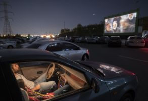 An Iranian couple sit at their vehicle in a Drive-in cinema in western Tehran, following the new coronavirus disease (COVID-19) outbreak in Iran, on May 1, 2020. Drive-in cinema organized by the Owj Arts and Media Organization which is one of the subordinate organizations of the Islamic Revolutionary Guards Corps (IRGC) held for the first time after the victory of Iran's Islamic Revolution.Drive-in cinema during the coronavirus lockdown, Tehran, Iran - 01 May 2020