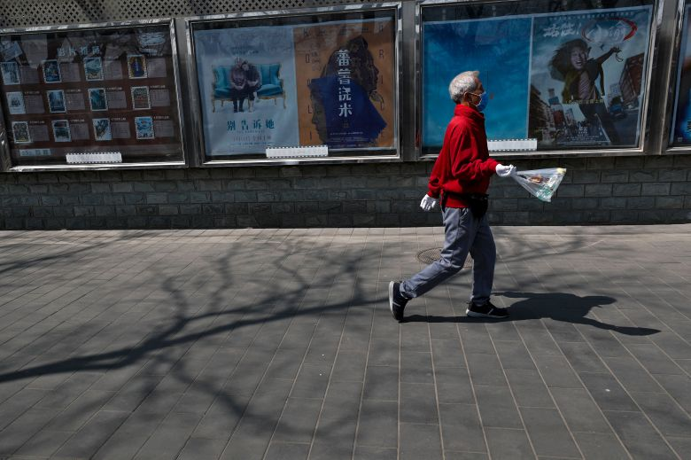 Man wearing a protective face mask to protect against the spread of the coronavirus walks past January movie posters outside a cinema in Beijing, . Cinemas across China still remain closed although most restaurants, stores and office buildings has reopened the businesses following the new coronavirus outbreakVirus Outbreak , Beijing, China - 06 Apr 2020
