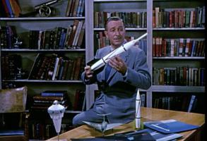 Walt Disney holds a rocket