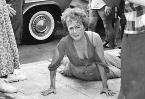 "Actress Olivia de Havilland lies on the sidewalk in the dramatic ending of her role in the movie ""Lady in a Cage,"" in which she spends hours trapped in an elevator, then rushes to the street where she is hit by a passing car, March 12, 1964. Here, she crawls on to the sidewalk as ""spectators"" look on. (AP Photo/Don Brinn)"