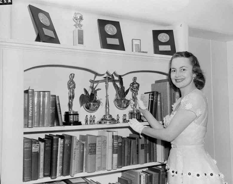 """Actress Olivia de Havilland puts her Academy Award Oscar on her shelf after a long night speaking to the press and receiving the congratulations of friends after winning her second award for """"The Heiress,"""" March 26, 1950. (AP Photo/Frank Filan)"""