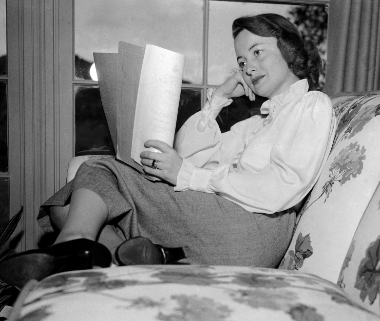 """Film actress Olivia DeHavilland curls up in the living room of her Beverly Hills, Calif. home while reading a script on April 16, 1948. The Oscar winner in the Academy awards will soon start """"The Heiress,"""" the current New York stage success which is the first film William Wyler has done since """"The Best Years of our Lives."""" DeHavilland is considering another movie to follow that one and then plans to play """"Romeo and Juliet"""" on Broadway. (AP Photo/Marcus Goodrich)"""