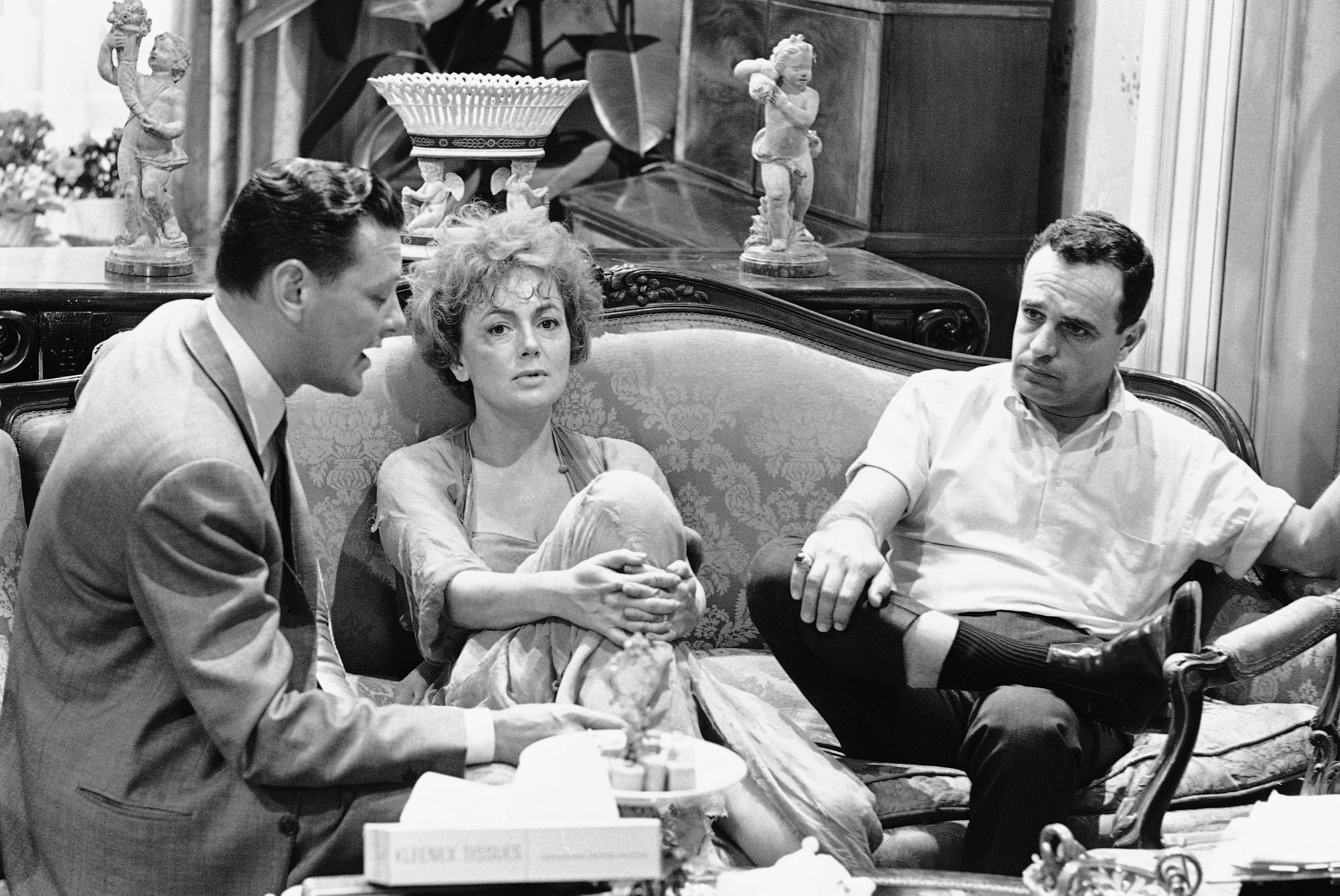 "Olivia De Havilland discusses her part in the film ""Lady In A Cage,"" with producer Luther Lavis (left) and director Walter Grauman in Hollywood, March 26, 1963. She spends most of the movie in a home elevator. De Havilland considers this role one of the most challenging of her career. (AP Photo/Don Brinn)"