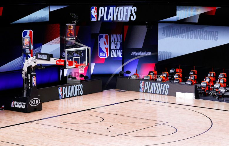 LAKE BUENA VISTA, FLORIDA - AUGUST 26: An empty court and bench is shown with the #WholeNewGame signage following the scheduled start time in Game Five of the Eastern Conference First Round between the Milwaukee Bucks and the Orlando Magic during the 2020 NBA Playoffs at AdventHealth Arena at ESPN Wide World Of Sports Complex on August 26, 2020 in Lake Buena Vista, Florida. The Milwaukee Buck have boycotted game 5 reportedly to protest the shooting of Jacob Blake in Kenosha, Wisconsin. NOTE TO USER: User expressly acknowledges and agrees that, by downloading and or using this photograph, User is consenting to the terms and conditions of the Getty Images License Agreement. (Photo by Kevin C. Cox/Getty Images)