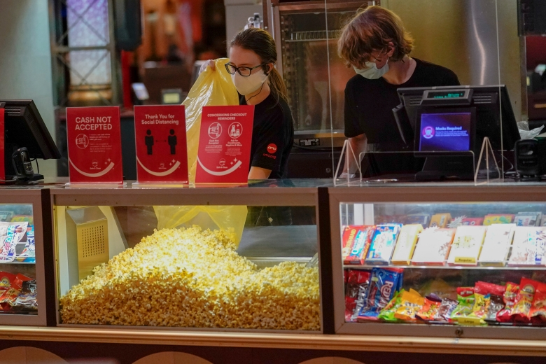 Concessions workers stock the bins with popcorn and other treats as the theatre opens for some of the first showings at the AMC theatre when it re-opened for the first time since shutting down at the start of the COVID-19 pandemic, Thursday, Aug. 20, 2020, in West Homestead, Pa. (AP Photo/Keith Srakocic)