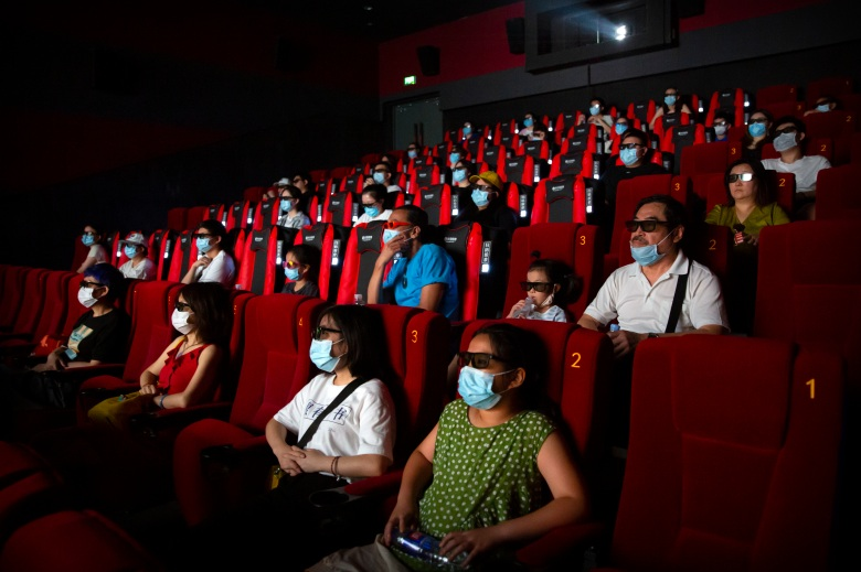 "People wearing face masks to protect against the coronavirus watch the film ""Dolittle"" at a movie theater in Beijing, Friday, July 24, 2020. Beijing partially reopened movie theaters Friday as the threat from the coronavirus continues to recede in China's capital. (AP Photo/Mark Schiefelbein)"