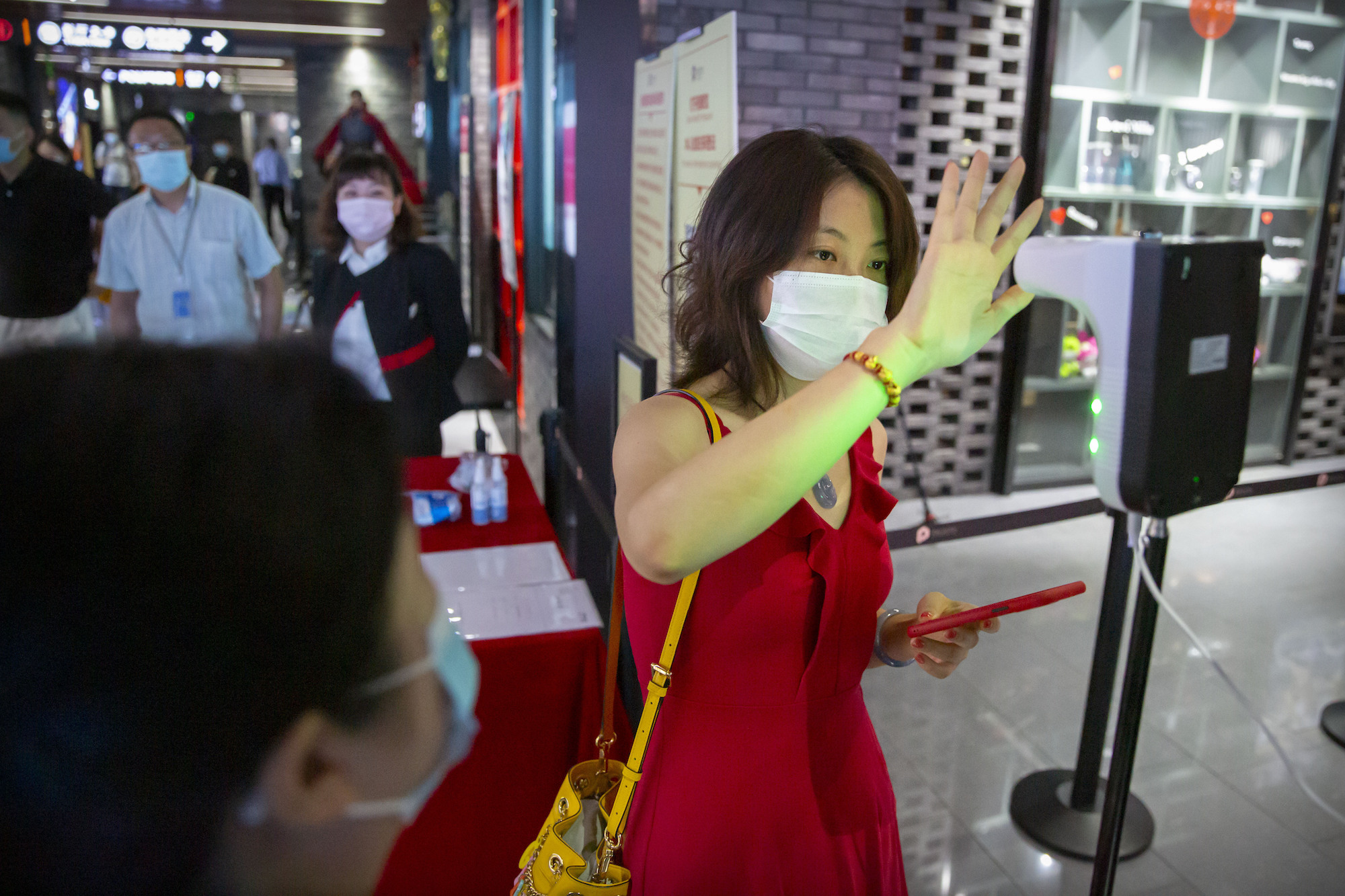 A patron wearing a face mask to protect against the coronavirus holds her hand to a temperature scanner as she enters a movie theater in Beijing, Friday, July 24, 2020. Beijing partially reopened movie theaters Friday as the threat from the coronavirus continues to recede in China's capital. (AP Photo/Mark Schiefelbein)