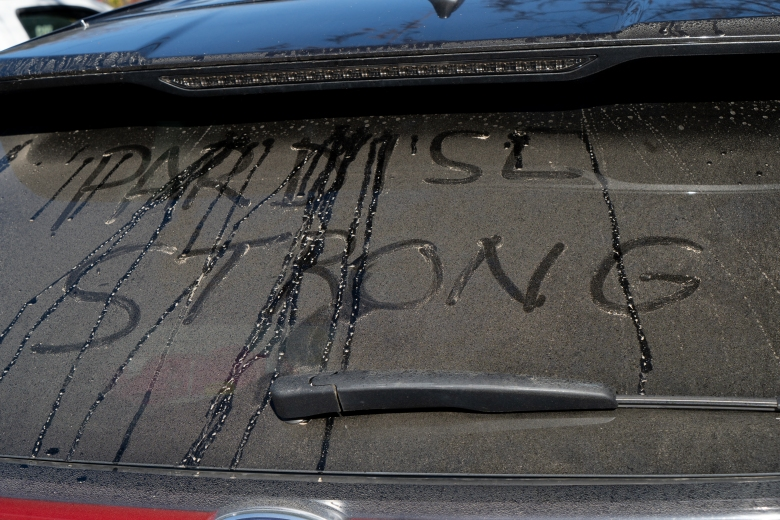 """Paradise, CA - A rear window of a vehicle with the words """"Paradise Strong"""" written in the dirt. (National Geographic/Sarah Soquel Morhaim)"""