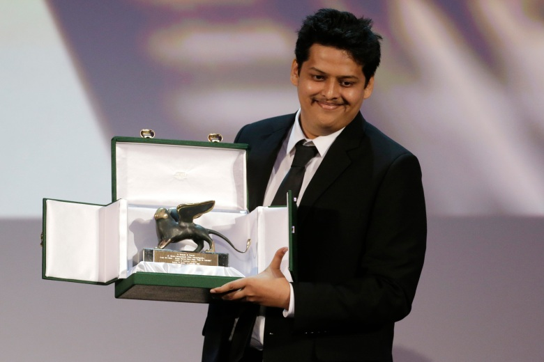 Director Chaitanya Tamhane poses for photographers with the Lion of the Future Award for his movie Court during the awards ceremony of the 71th edition of the Venice Film Festival in Venice, Italy, Saturday, Sept. 6, 2014. (AP Photo/David Azia)