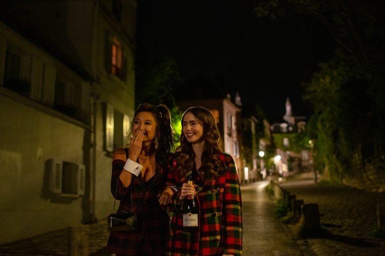 EMILY IN PARIS (L to R) ASHLEY PARK as MINDY and LILY COLLINS as EMILY in episode 105 of EMILY IN PARIS Cr. CAROLE BETHUEL/NETFLIX © 2020